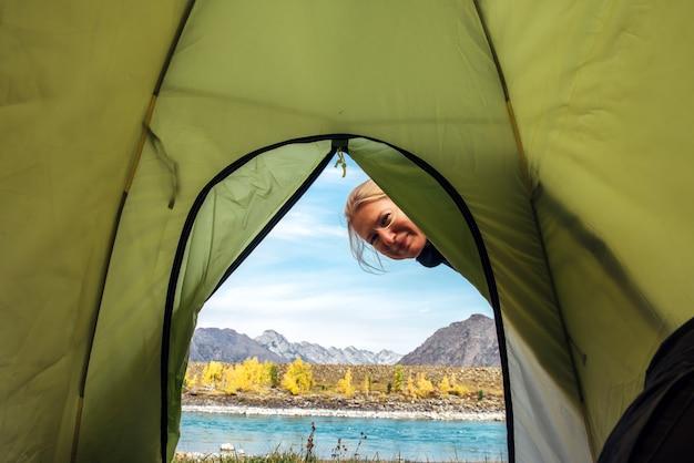 Kobieta Patrzy W Zielony Namiot I Uśmiecha Się. Widok Z Wewnątrz Namiotu Na Górach I Rzece W Słoneczny Jesienny Dzień. Premium Zdjęcia