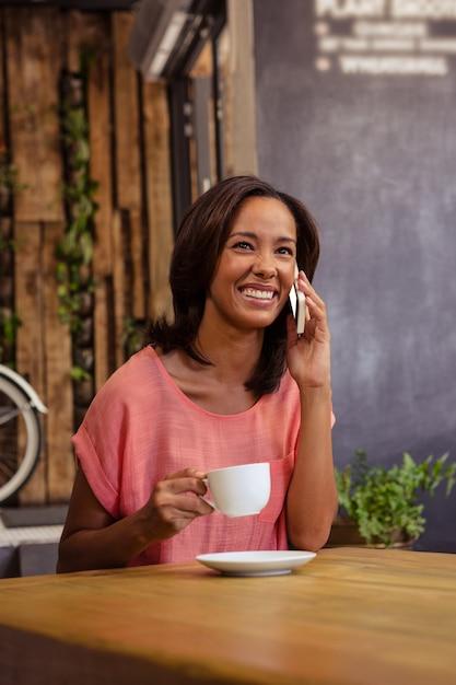 Kobieta Pije Kawę I Używa Smartphone Premium Zdjęcia