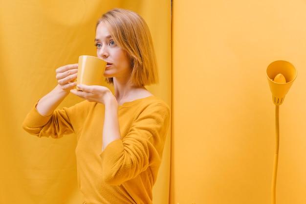 Kobieta pije od kubka w żółtej scenie Darmowe Zdjęcia