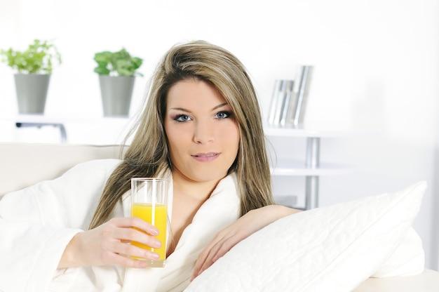 Kobieta Pije Sok Pomarańczowego I Relaksuje Na Białej Kanapie Premium Zdjęcia