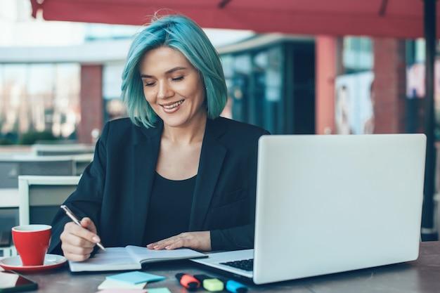 Kobieta Pisze Coś Podczas Korzystania Z Laptopa I Siedząc W Kawiarni Premium Zdjęcia