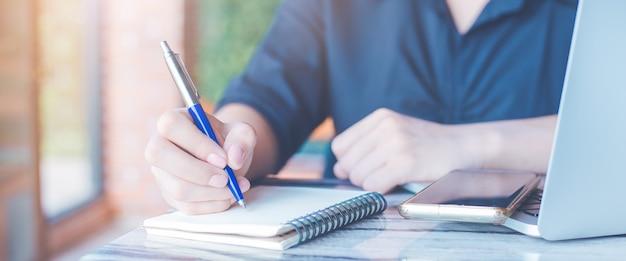 Kobieta Pisze Długopisem W Biurze Na Notatniku, Na Stole Telefony Komórkowe I Laptopy, Baner Internetowy. Premium Zdjęcia