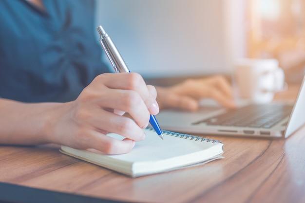Kobieta Pisze Na Notatniku Piórem I Używa Laptopa Do Pracy W Biurze. Premium Zdjęcia