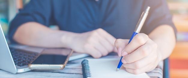 Kobieta Pisze Na Notesie Piórem I Używa Telefonu Komórkowego W Banerze Office.web. Premium Zdjęcia
