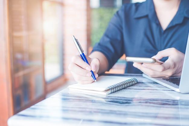Kobieta Pisze Na Zeszycie Piórem I Korzysta Z Telefonu Komórkowego W Biurze. Premium Zdjęcia