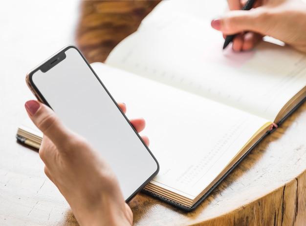 Kobieta pisze z makiety telefonu Darmowe Zdjęcia