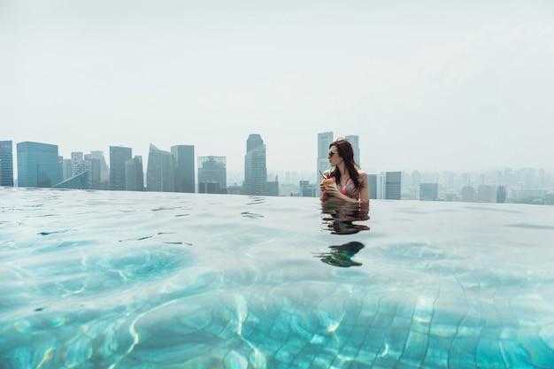 Kobieta Pływanie W Odkrytym Basenie Na Dachu W Singapurze. Młoda Kobieta Z Kokosem W Dłoniach Relaksuje Się W Odkrytym Basenie Na Dachu Premium Zdjęcia