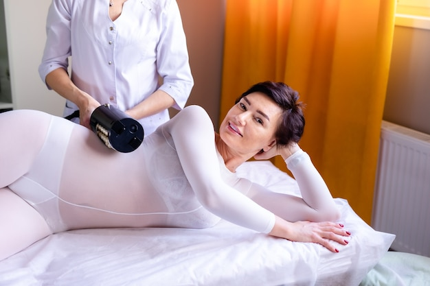 Kobieta Po Zabiegu Masażu Antycellulitowego Lpg Lub R-smooth Z Aparatem Premium Zdjęcia
