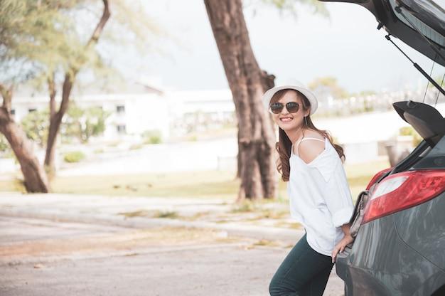 Kobieta podróżnik siedzi na samochodzie hatchback Premium Zdjęcia