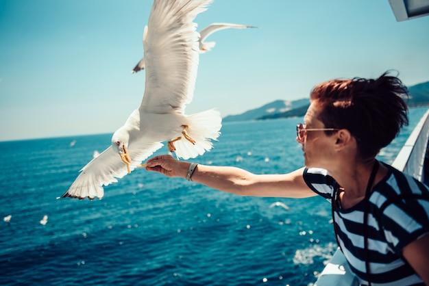 Kobieta podróżuje na ferryboat i karmi seagulls Premium Zdjęcia