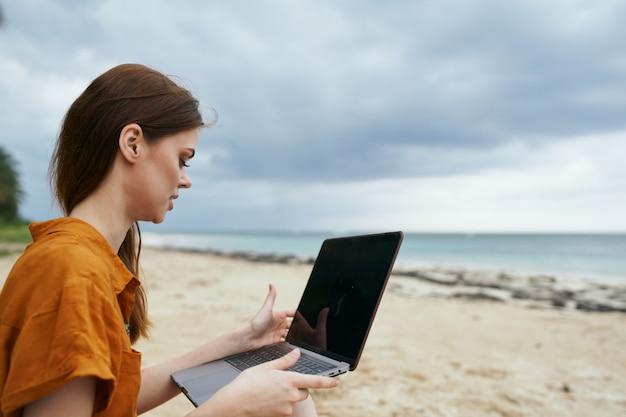 Kobieta Podróżuje Z Laptopem Wzdłuż Oceanu Wzdłuż Piasku Z Palmami Premium Zdjęcia