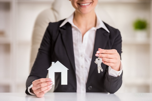 Kobieta pokazuje do domu na sprzedaż znak i klucze. Premium Zdjęcia
