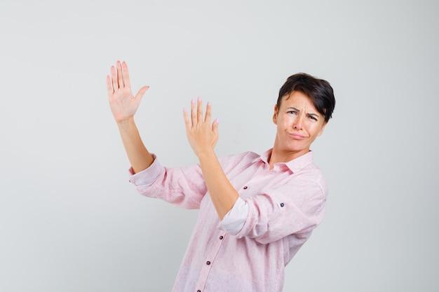 Kobieta Pokazuje Gest Chop Karate W Widoku Z Przodu Różowej Koszuli. Darmowe Zdjęcia