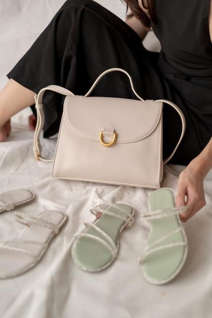 Kobieta Pokazuje Rzemienną Mody Torbę, Sandały I Premium Zdjęcia