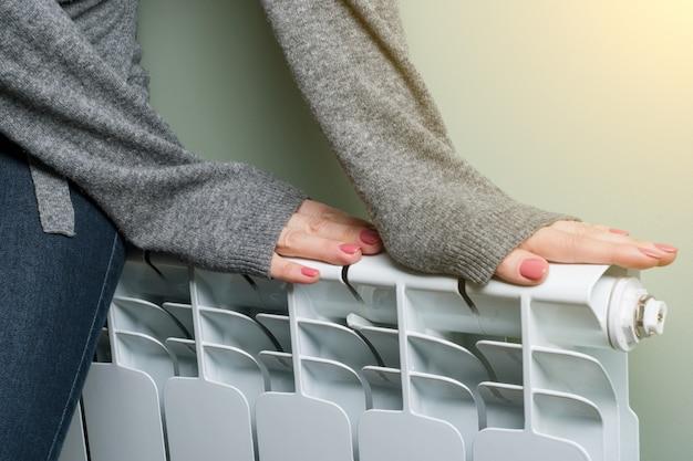 Kobieta położyła ręce na grzejniku Premium Zdjęcia