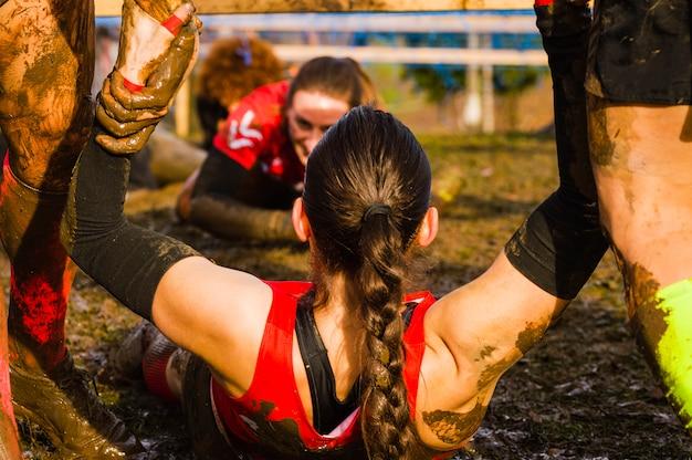 Kobieta pomogła przez pomocna dłoń w wyścigu błotnistym xtreme Premium Zdjęcia