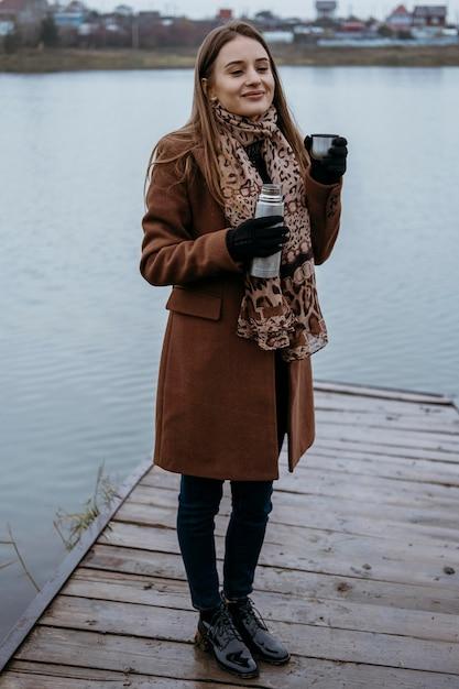 Kobieta Pozuje Nad Jeziorem Z Gorącym Napojem Premium Zdjęcia