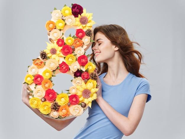 Kobieta Pozuje Z Bukietem Kwiatów, Numer 8, Dzień Kobiet Premium Zdjęcia