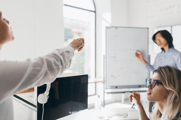 Kobieta Pracownik Biurowy W Białej Bluzce Wskazując Palcem Na Pokładzie Podczas Spotkania Z Kolegami Darmowe Zdjęcia