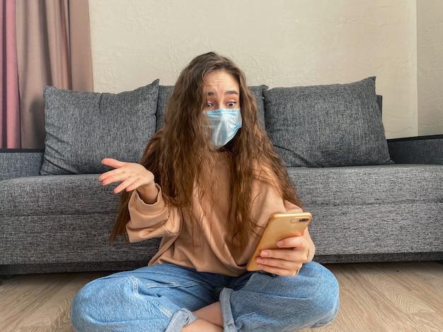 Kobieta Pracująca W Domu Nosi Ochronną Maskę Medyczną. Koncepcja Kwarantanny Domowej Premium Zdjęcia