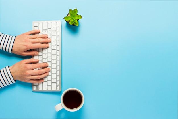 Kobieta Pracuje W Biurze Na Niebieskim Tle. Koncepcja Obszaru Roboczego, Praca Przy Komputerze, Niezależny Premium Zdjęcia