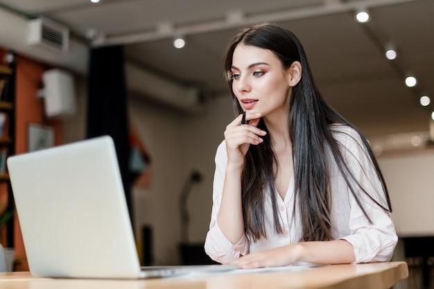 Kobieta pracuje w biurze z laptopem Premium Zdjęcia