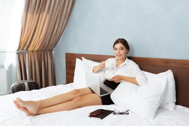 Kobieta pracuje w pokoju hotelowym Premium Zdjęcia