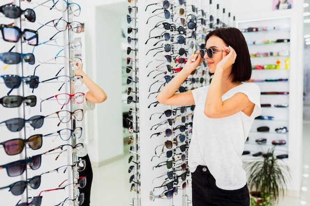 Kobieta Próbuje Na Okularach Przeciwsłonecznych W Sklepie Darmowe Zdjęcia