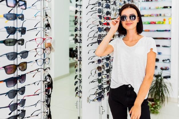 Kobieta Próbuje Okulary Przeciwsłonecznych Przy Sklepem Darmowe Zdjęcia