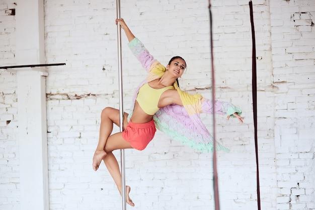 Kobieta przecina jej nogi wokół słupa, podczas gdy ona tańczy w studiu Darmowe Zdjęcia