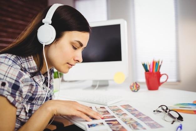 Kobieta Przegląda Fotografie W Biurze Premium Zdjęcia