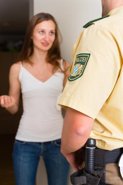 Kobieta przesłuchanie policjanta w drzwiach Premium Zdjęcia