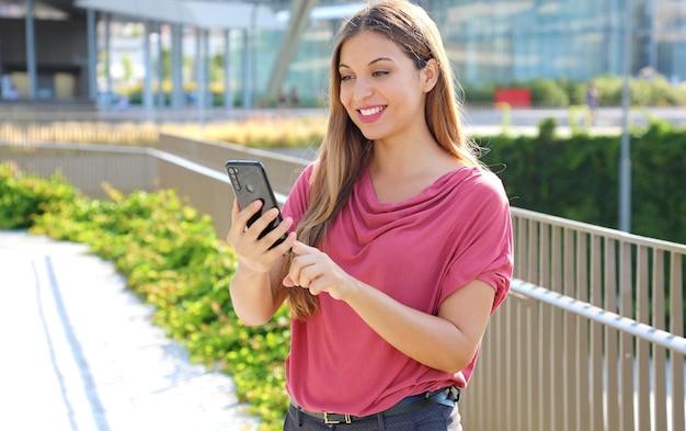 Kobieta Przewija Wiadomości W Aplikacji Na Smartfona, Aby Rozmawiać Na Ulicy Miasta Premium Zdjęcia