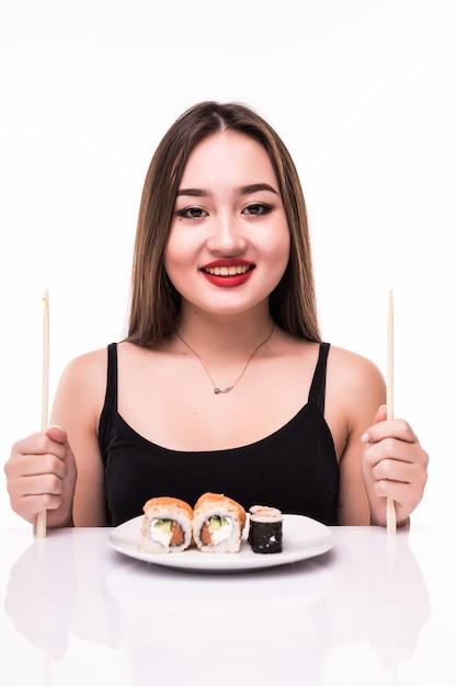 Kobieta Przygotowuje Się Do Spożycia Rolki Sushi Smak Za Pomocą Drewnianych Pałeczek Na Białym Tle Darmowe Zdjęcia