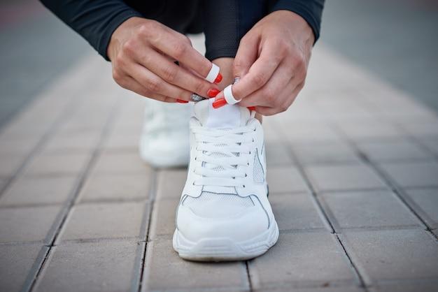Kobieta przygotowuje się do uruchomienia. kobiece ręce wiązanie sznurowadeł na sportowe trampki Premium Zdjęcia