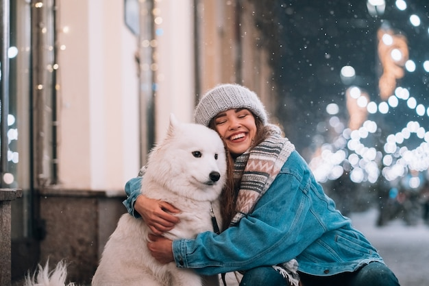 Kobieta Przytula Swojego Psa Na Ulicy W Nocy Darmowe Zdjęcia
