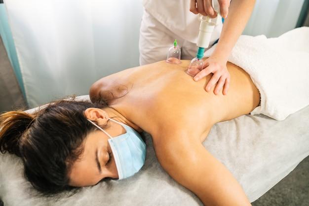 Kobieta Rasy Kaukaskiej Poddawana Fizjoterapeutycznemu Masażowi Podciśnieniowemu Strzykawką Z Kubkiem Próżniowym W Celu Masowania Pleców Klienta Leżącego Na Noszach Z Maską Na Twarz Z Powodu Wirusa Covid 19 Premium Zdjęcia