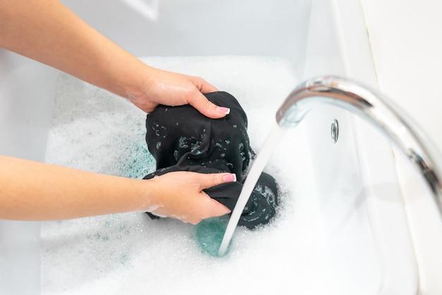 Kobieta Ręce Do Prania Czarnych Ubrań W Misce Premium Zdjęcia