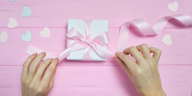Kobieta Ręce Owijania łuk Na Pudełko Z Papieru Serca Premium Zdjęcia