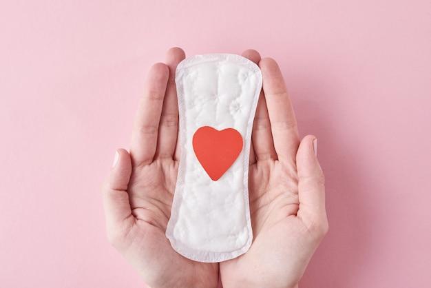 Kobieta Ręce Trzymać Podpaski Z Czerwonym Sercem Na Różowym Tle Premium Zdjęcia