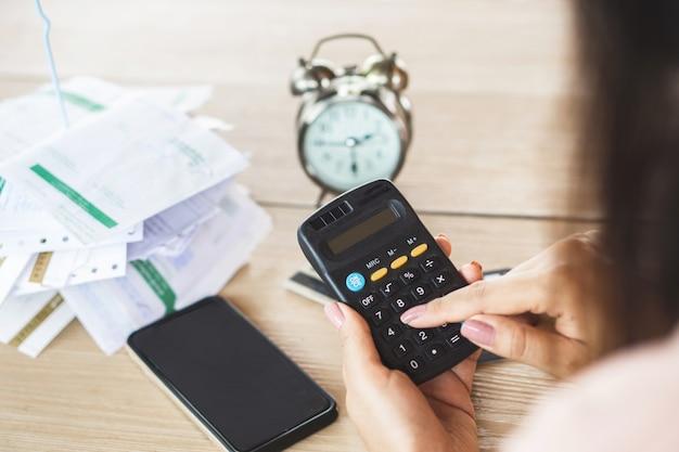 Kobieta ręka trzyma kalkulator licząc dług Premium Zdjęcia
