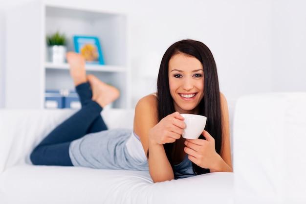 Kobieta Relaks Na Kanapie Z Filiżanką Kawy Darmowe Zdjęcia