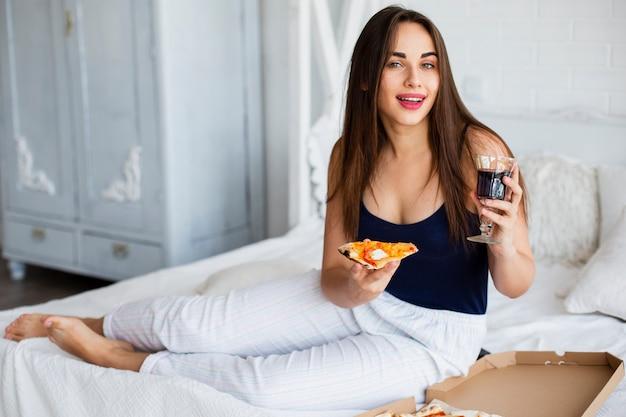 Kobieta relaksuje w łóżku z winem i pizzą Darmowe Zdjęcia