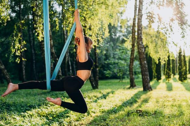 Kobieta robi fly jogi w parku na świeżym powietrzu. widok z boku Premium Zdjęcia
