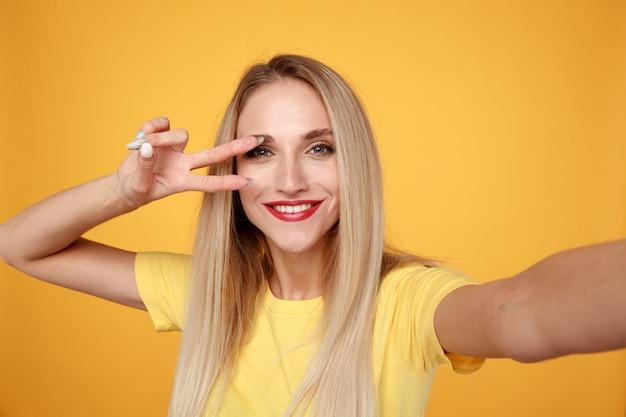 Kobieta Robi Selfie I Bawić Się Na żółtym Tle Premium Zdjęcia