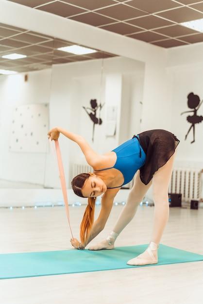 Kobieta robi trening z gumką w siłowni Premium Zdjęcia