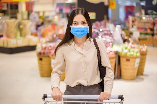 Kobieta Robi Zakupy W Supermarkecie Z Maską Premium Zdjęcia