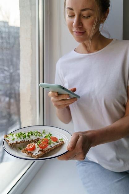 Kobieta Robi Zdjęcie Na Smartfonie, Trzymając Talerz Z Chrupiącym Chlebem żytnim Z Serem I Mikro Zieleniną Premium Zdjęcia