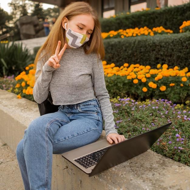 Kobieta Robi Znak Pokoju Podczas Rozmowy Wideo Na Laptopie Darmowe Zdjęcia