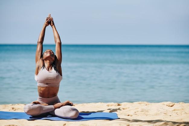 Kobieta Rozciągająca Się Na Plaży Premium Zdjęcia